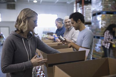 People at a nonprofit food bank pack boxes
