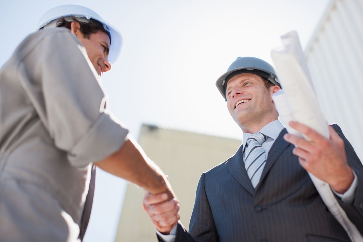 Contractor shaking hands and building a networking with an engineer on a job site.