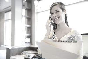 Receptionist with medical record talking on telephone