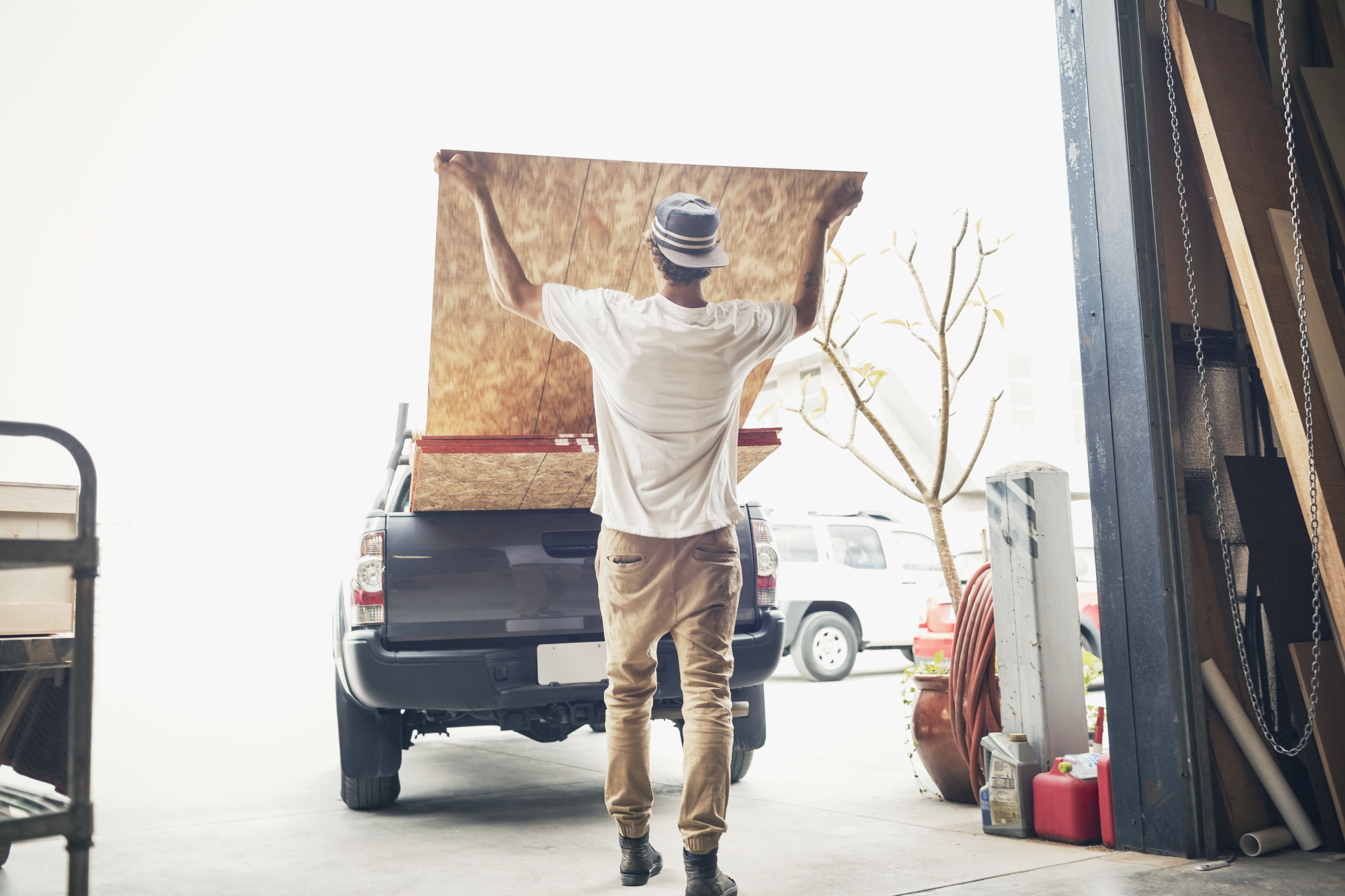 Rear view of man loading plywood sheets into a pickup truck