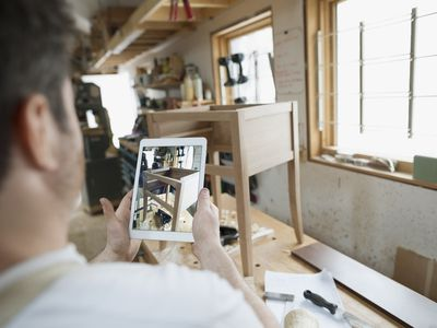 Man using a tablet to photograph furniture to sell on eBay.