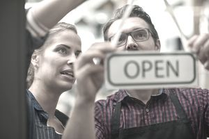 a businessman and woman hanging up an open sign