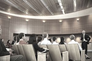 Group of executives listening to man leading seminar in auditorium