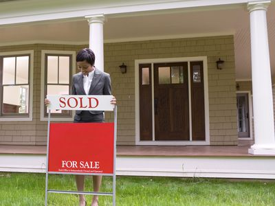A real estate assistant placing sold sign on a home for sale sign.