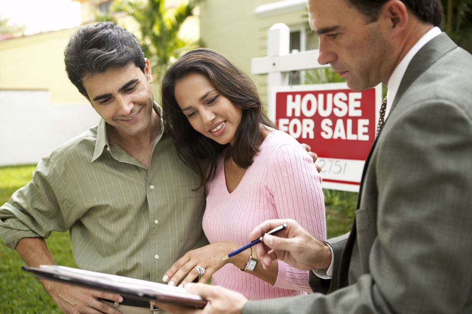 Couple and realtor signing papers for new house