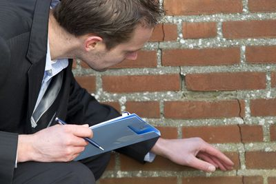 Insurance adjuster inspecting crack in brick wall.