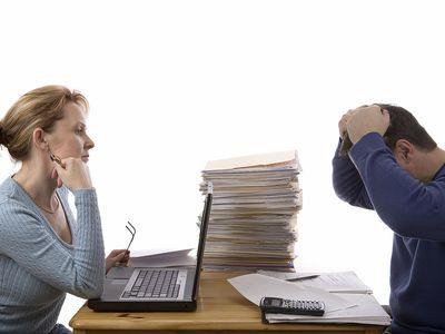 Flustered couple with stack of files, calculator, and laptop trying to figure out their business taxes on personal Tax Return