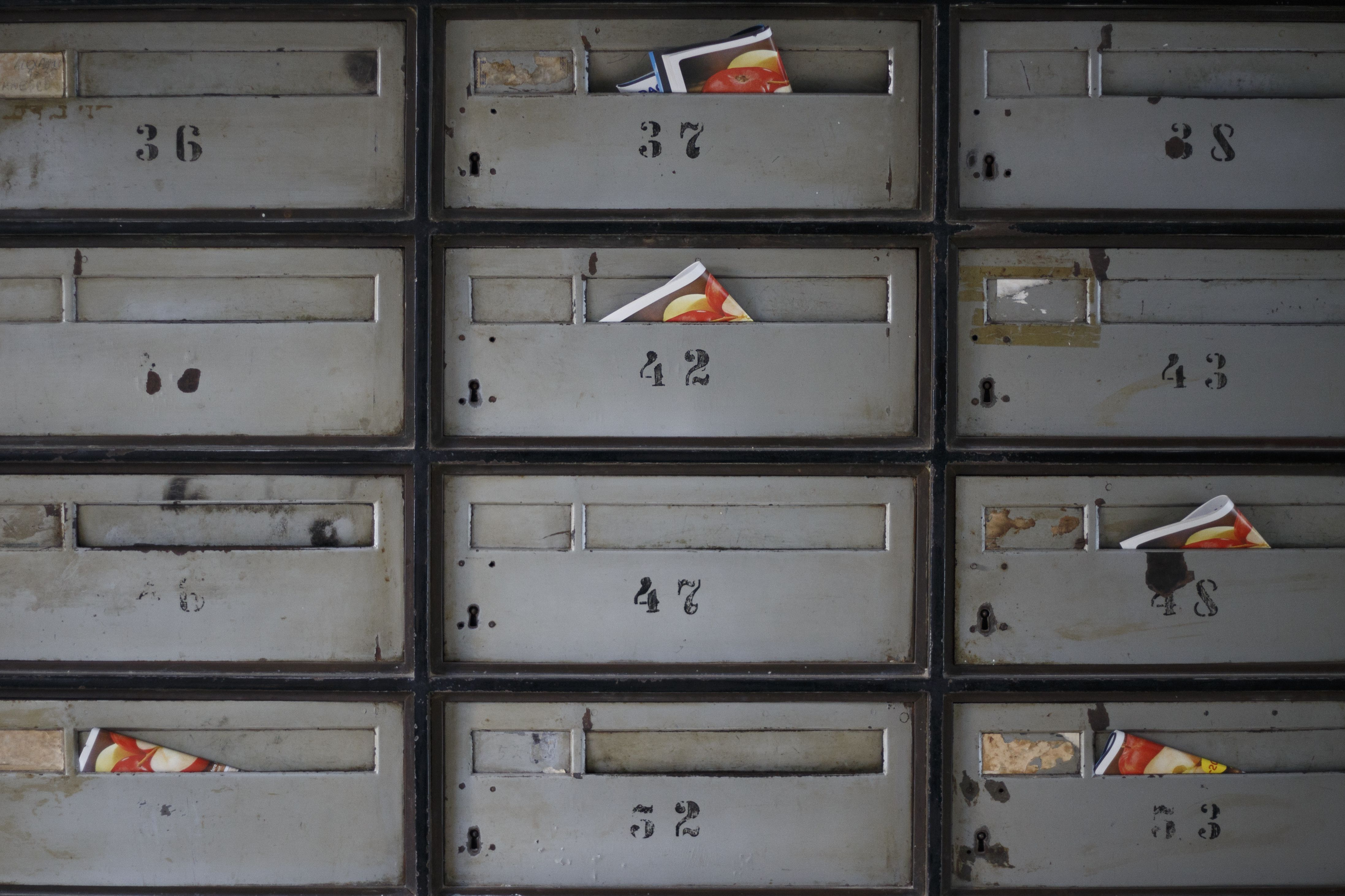 A close up of an apartment mail box bank with direct marketing mail sticking out of the boxes.