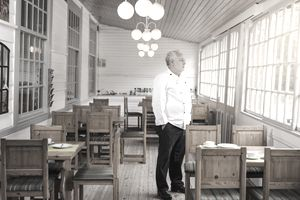 Man in white chef's coat in empty restaurant staring out the window