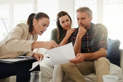 Real estate agent talking to clients and explaining the loan to value on the mortgage.