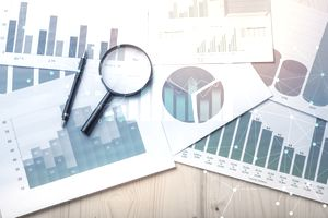 Charts and graphs with a magnifying glass laying on a table indicating doing market research.