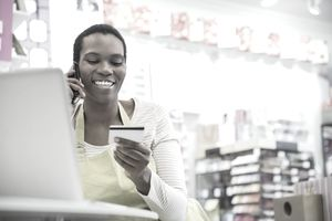 Woman making a credit card payment in front of laptop