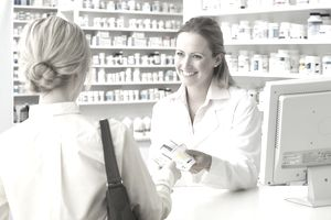Pharmacist handing woman medication