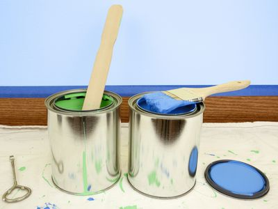 Two cans of paint on a drip cloth
