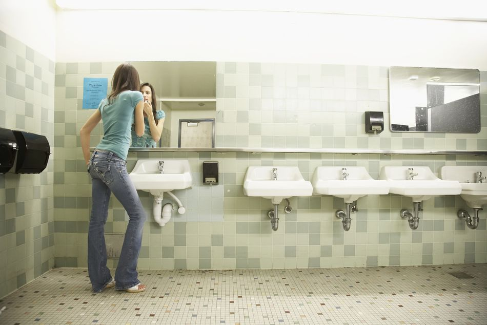 Teenaged girl using mirror in school bathroom