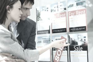 Couple looking at postings of rental properties for sale homes