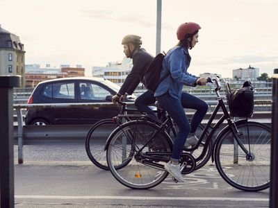 Man and woman commuting on bikes, going in opposite directions, with car on the road in the background