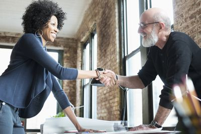 Two people shaking hands across a drafting table after the successful sale of a business.