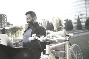 Man working on laptop at park with bicycle