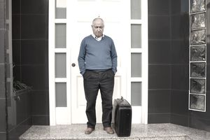Man outside of property with suitcase