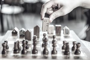 Person playing chess using houses as pieces representing real estate disputes.