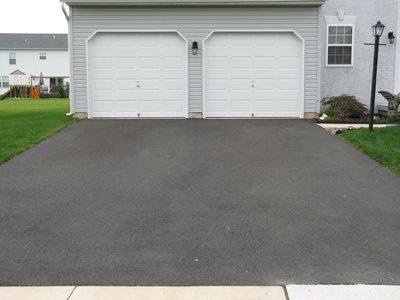 A double garage with white doors at the end of a seal coated driveway