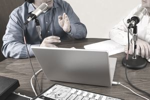 Two Men recording a podcast, sitting at table with two microphones, laptop, sound board, and script