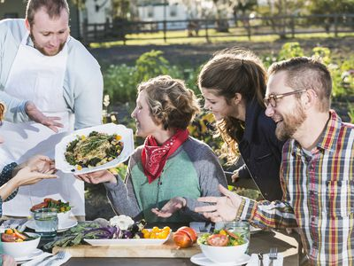 Chef serving locally grown food to group of people