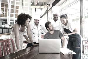 Restaurant staff including chefs, waitresses and manager, gathering around laptop on a table in the dining area.