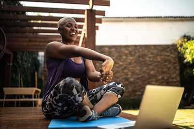 A woman stretches her arms while looking down at her laptop, where she's filming herself as a virtual personal trainer