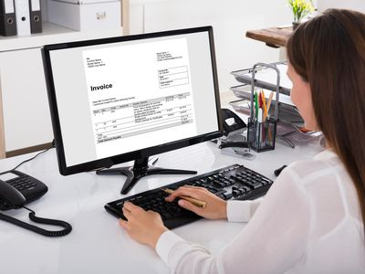 Businesswoman Looking At Invoice On Computer