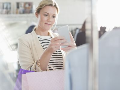 woman shopping and taking photo with cell phone