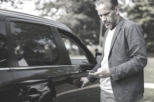 Businessman using smart phone while opening car door at park