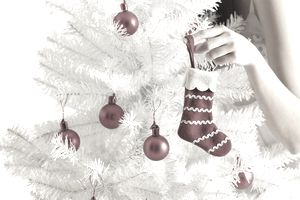 Woman hanging red ornament on white Christmas tree