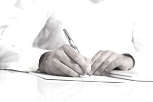 Businessman holding a pen & taking notes on paper