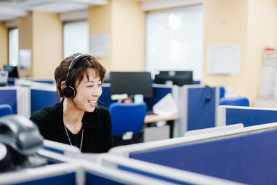 A business woman wearing a headset for video chat in the office