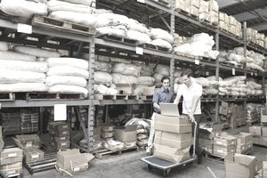 Two men in a warehouse using a laptop and comparing the EOQ metric with the actual on-hand inventory