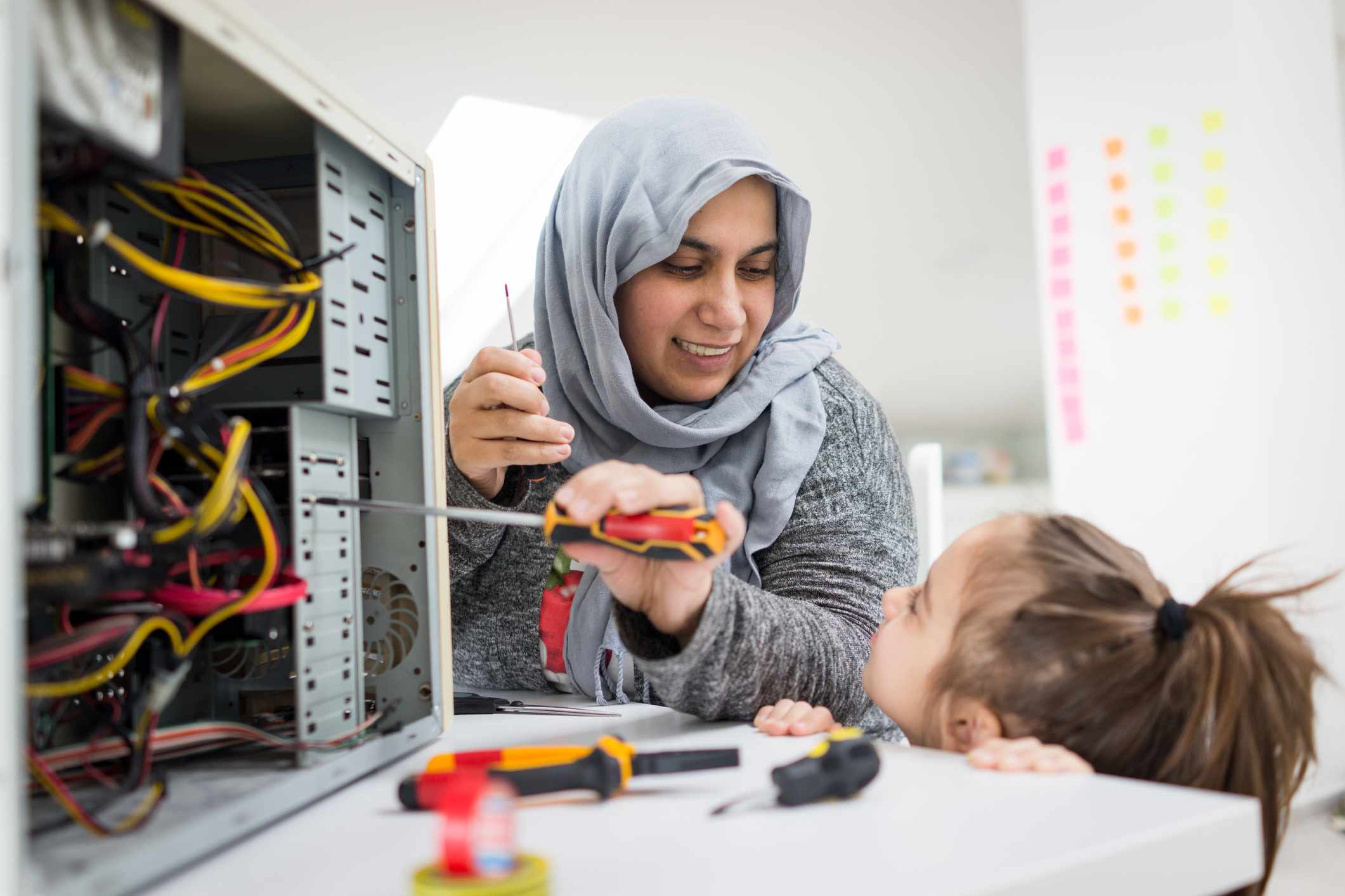 Woman wearing burka repairing a computer while child watches.