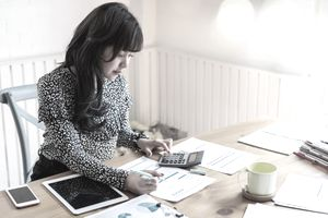 Woman reviewing business tax paperwork at her desk