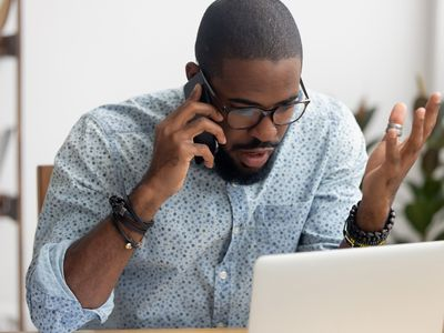 Angry African-american businessman talking on cellphone in office
