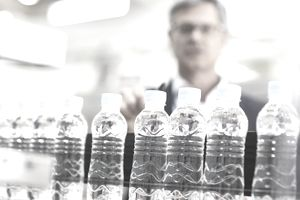 Supervisor examining bottles in factory