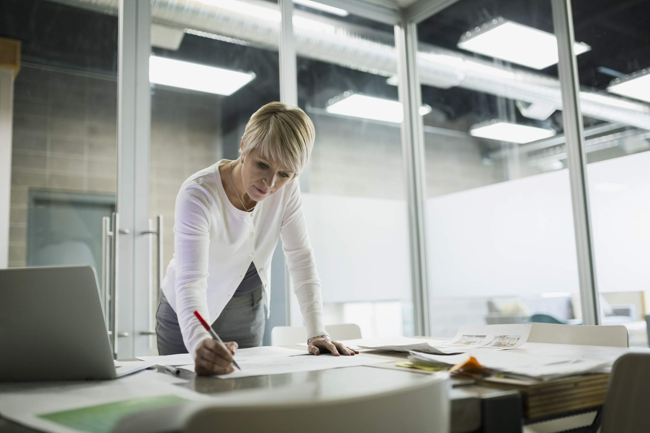 Woman standing over a desk, editing in office