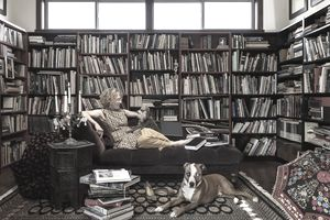 Woman on couch with dogs in home library