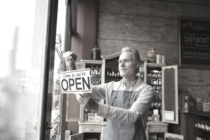 Male shop owner hanging open sign in spice shop window