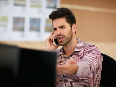 a man looking frustrated on phone