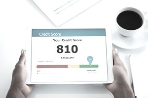 woman holding tablet displaying 810 credit score