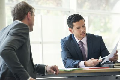 Businessmen discussing tax documents in a meeting