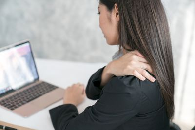Woman working at desk experiencing shoulder pain