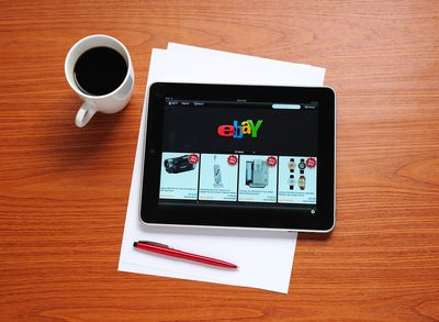 tablet showing eBay logo with coffee, paper, and a pen on a desk