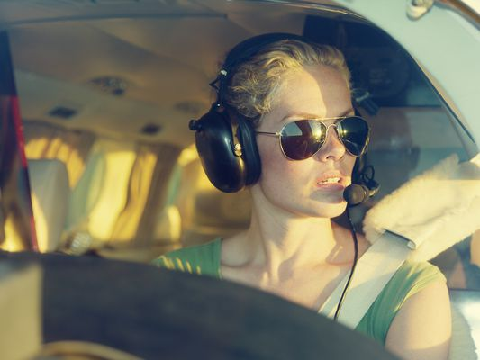 A female pilot is seated in the cockpit. She's wearing sunglasses and wearing headphones.